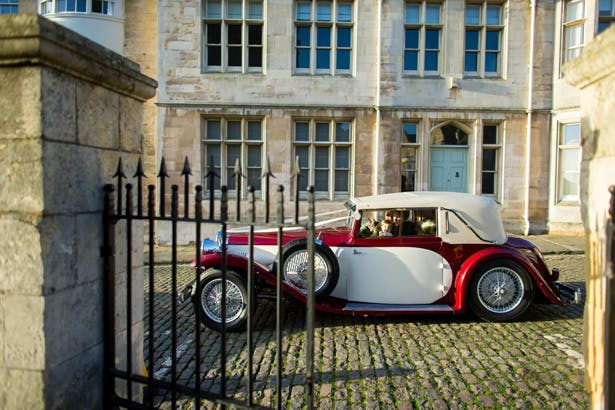 Red and white vintage wedding car| Abigail and Chris's Real Christmas Wedding | Confetti.co.uk