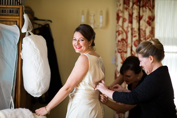 Bridesmaids helping the bride with her dress | Abigail and Chris's Real Christmas Wedding | Confetti.co.uk