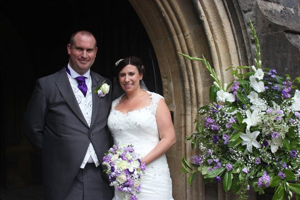 The newlyweds outside the church after the ceremony | Purple themed wedding| Rhiannon & Michael's Real Wedding | Confetti.co.uk
