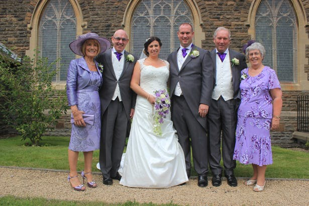Bride and groom with their parents outside the church after the ceremony | Purple themed wedding| Rhiannon & Michael's Real Wedding | Confetti.co.uk