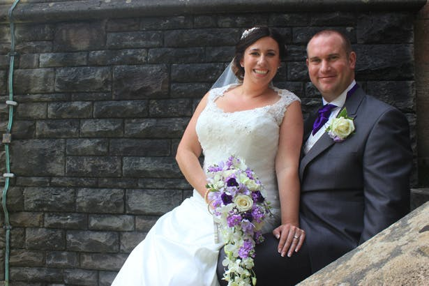 Bride and groom on the staircase outside the church | Purple themed wedding| Rhiannon & Michael's Real Wedding | Confetti.co.uk
