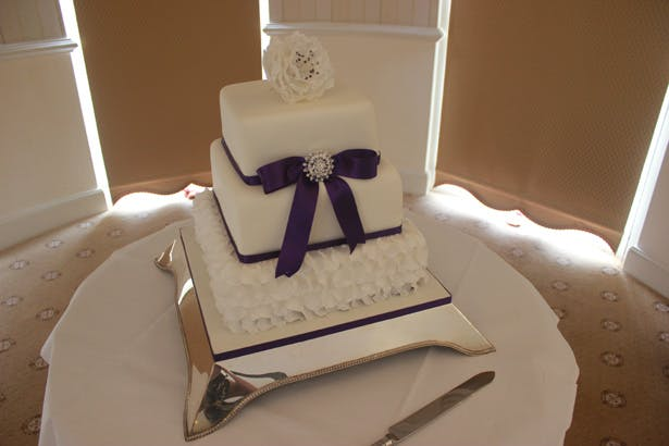 White and purple 3 tiered wedding cake| Purple themed wedding| Rhiannon & Michael's Real Wedding | Confetti.co.uk
