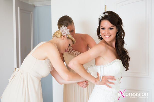 Bridesmaids help the bride with her dress | Confetti.co.uk