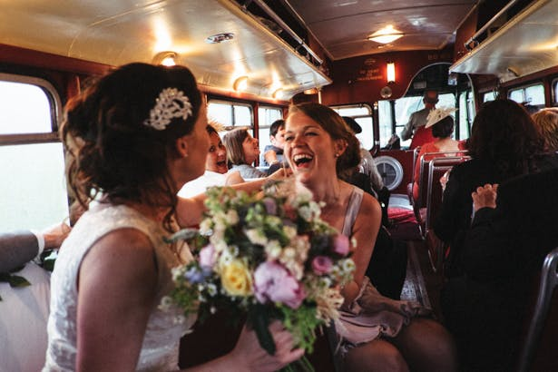 The bride and the bridesmaid enjoying the drive to the reception in the vintage red London bus | Fun wedding ideas | Steph and Gary's Real Garden Wedding | Confetti.co.uk