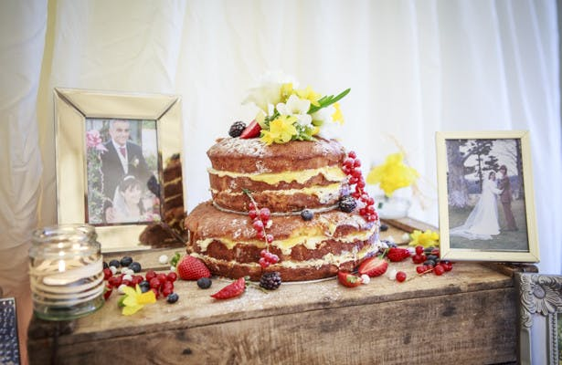 Naked wedding cake with berries and spring flowers | Spring wedding theme ideas | Wedding at the Deer Park country house | Nadine and Roberts Real Wedding | Confetti.co.uk