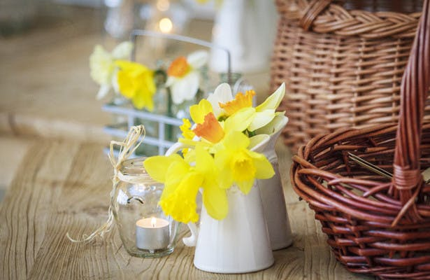 Daffodils in small jugs and wicker baskets centrepieces | Spring wedding theme ideas | Wedding at the Deer Park country house | Nadine and Roberts Real Wedding | Confetti.co.uk