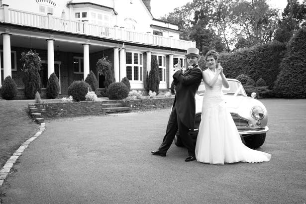 The bride and groom posing in front of the vintage wedding car  | Lizzie and Greg's Real Wedding | Confetti.co.uk