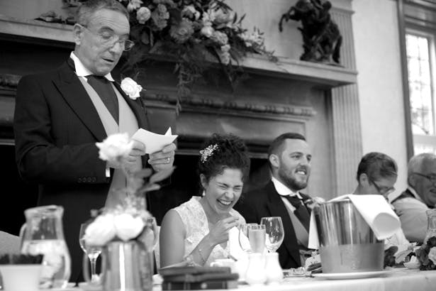 The bride laughing during the father of the brides speech | Lizzie and Greg's Real Wedding | Confetti.co.uk