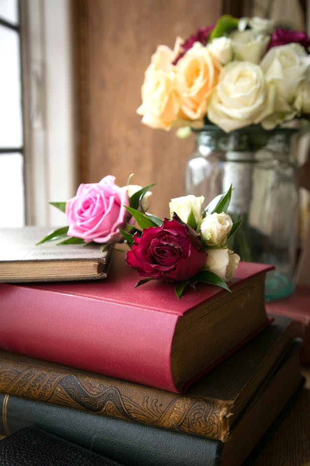 Pink coloured roses on vintage books | Lizzie and Greg's Real Wedding | Confetti.co.uk