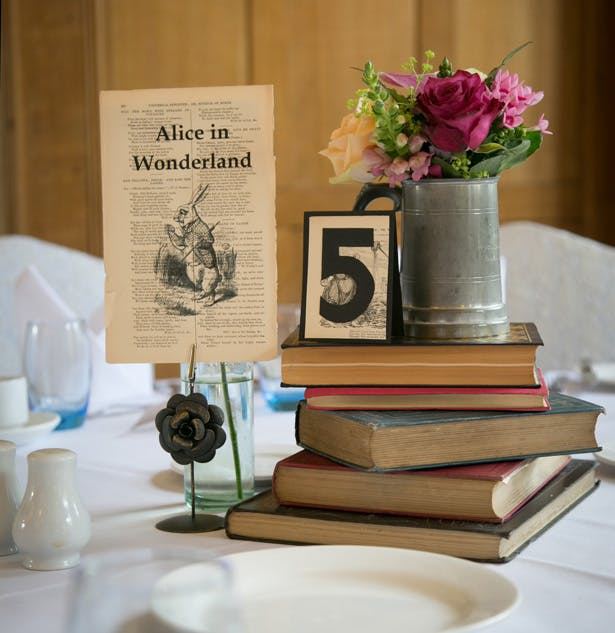 Vintage table decor ideas | Alice in wonderland page extract with vintage books table decor |  Vintage ideas | Lizzie and Greg's Real Wedding | Confetti.co.uk