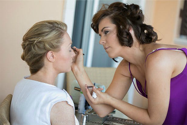 Chief bridesmaid applying the bride's makeup | Confetti.co.uk