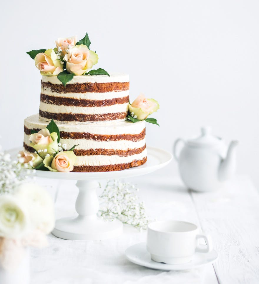 Modest Naked Wedding Cake - Rustic Wedding Cake with Flowers by Melnikov Sergey on Shutterstock | Confetti.co.uk