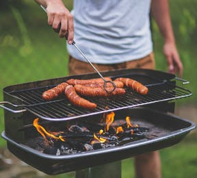Man grilling sausages on a barbecue grill | Confetti.co.uk