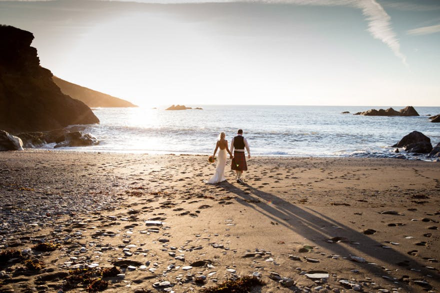 Couple Walking Along the Beach Toward the Ocean - Evolve Photography - Devon - Coast | Confetti.co.uk
