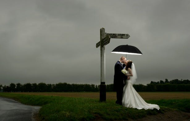 Evening wedding bride and groom kissing in the rain under umbrella by Fabulous Wedding Photography   Confetti.co.uk