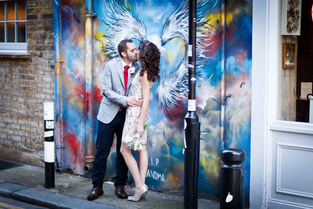 Bride and groom in front of street art at Veronica and Alejandro's real wedding| Confetti.co.uk