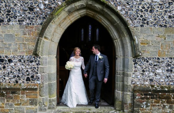 Beautiful Bride And Groom Leave Stone Brick Church | Confetti.co.uk