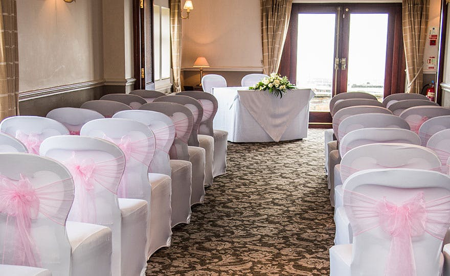 Pennine Manor Hilltop Wedding Ceremony Room with Pink and White Chair Decor | Confetti.co.uk