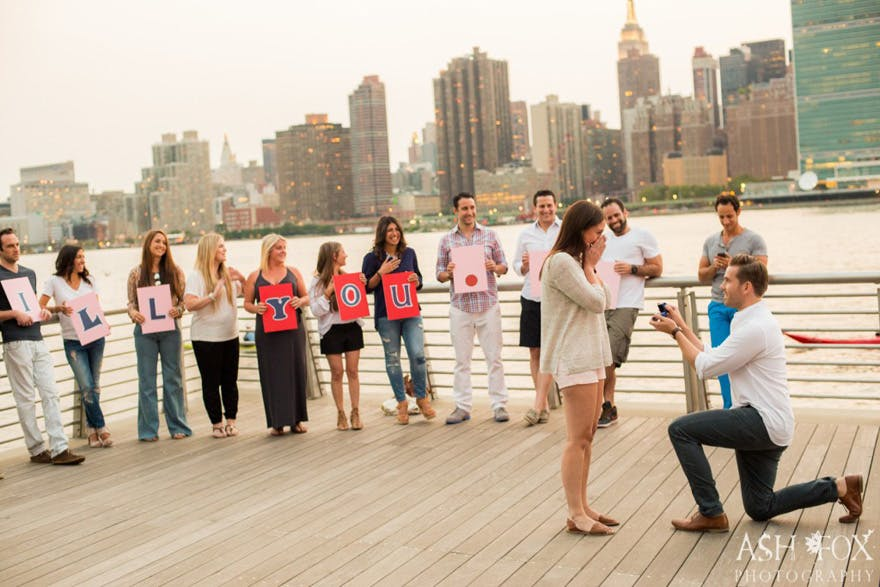 Will You Marry Me Signs with Family and Friends - Long Island City Surprise Proposal with Skyline Views by Ash Fox Photography | Confetti.co.uk