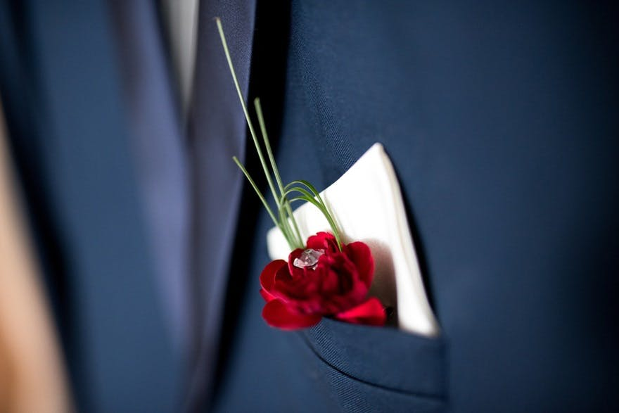 Red flower and handkerchief buttonholes | Confetti.co.uk
