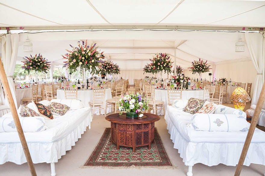 Lulu Pearl Tent from Arabian Tents - Moghul Marquee Party Tent and Luxury Wedding Marquee - Spring Themed Rustic Wedding Tent with Elaborate Floral Displays and Couches - Photo via lighttrick.co.uk | Confetti.co.uk