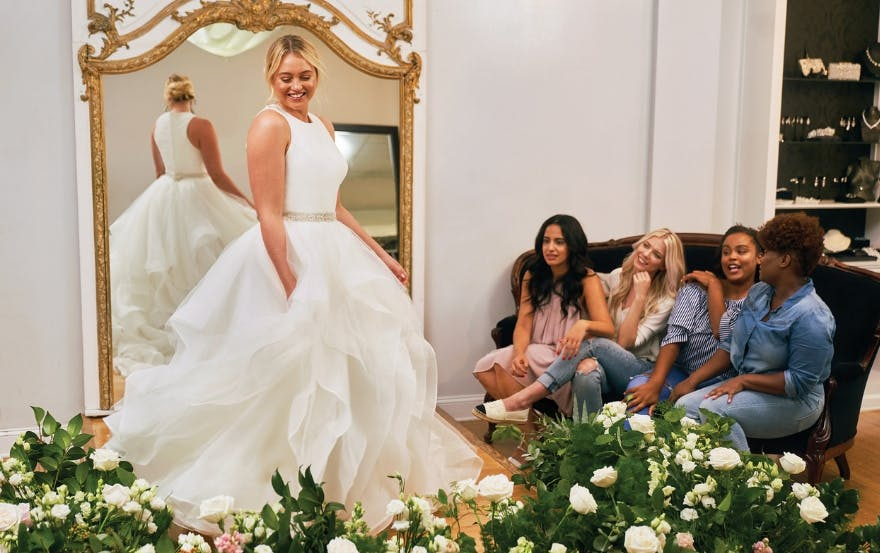 Bride trying on full-skirted Justin Alexander dress