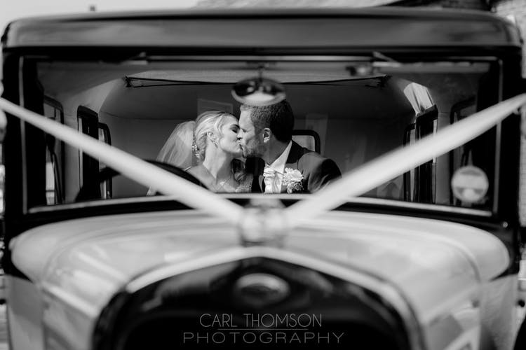 The open roof allows natural light into the wedding car