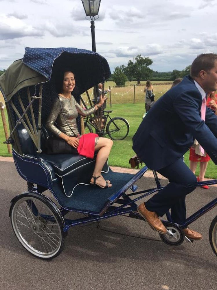 Wedding guest poses for the camera in the vintage rickshaw.