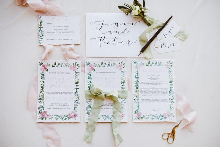 Traditional romantic invitations featuring hand-lettered calligraphy and watercolour roses